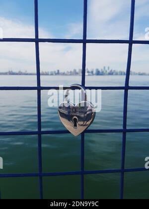 Primer plano del candado con forma de corazón en Fence by Sea Against Sky