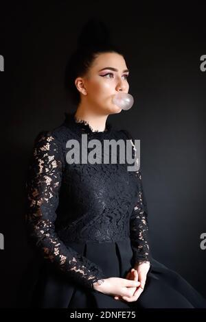 Chica que mira lejos mientras sopla Burbuja Gum contra fondo negro