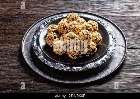 Trufas de chocolate negro recubiertas de almendras trituradas servidas en un plato negro sobre un fondo de madera oscura, vista superior, primer plano