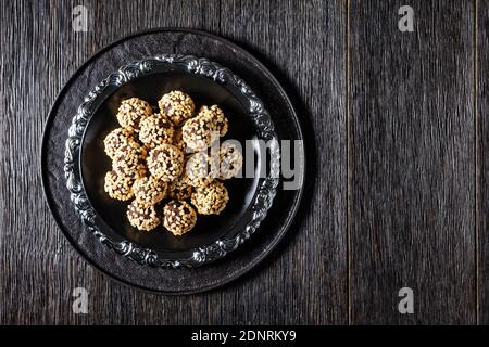 Dark chocolate truffles coated by crushed almonds served on a black plate on a dark wooden background, top view, close-up, copy space