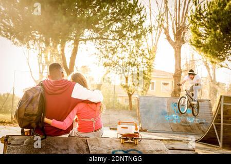 Vista trasera de la pareja joven sentada en Skateboard Park durante la puesta de sol