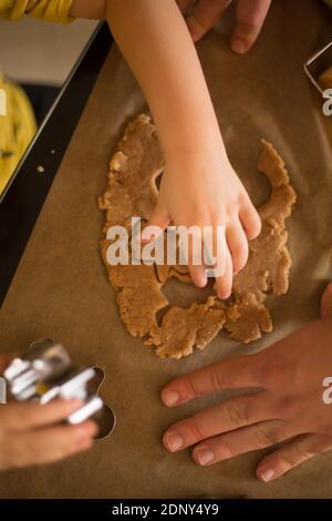 Manos recortadas haciendo galletas de jengibre
