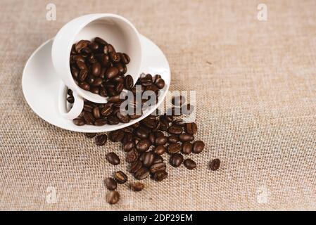 Desbordamiento de granos de café en una copa blanca sobre un saco de Burlap. Concepto de bebida favorita y agricultura