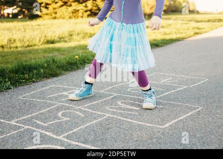 Primer plano de niña jugando saltando hopscotch al aire libre. Divertido juego de actividades para los niños en el patio de recreo al aire libre. Verano patio trasero deporte de calle para los niños