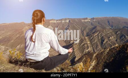 Joven morena con plait en camisa blanca medita sentada en un acantilado contra las lejanas montañas antiguas bajo el claro cielo azul vista posterior