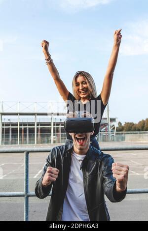 Alegre Mujer de pie detrás de novio con gafas VR