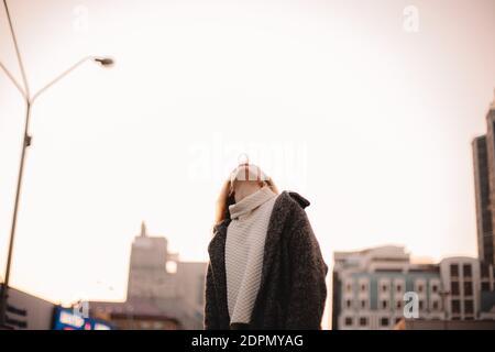 Niña adolescente soplando goma de burbujas contra el cielo despejado en la ciudad en otoño