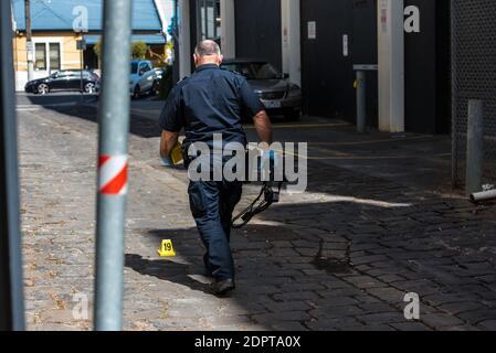 """Melbourne, Australia. 19 de diciembre de 2020. Un agente de policía de la unidad de investigación del delito inspecciona una escena del crimen en la zona de Windsor/Prahran donde se marcaron extensos rastros de sangre y se le encontró un hombre con heridas graves en las manos y después de una investigación policial se encontró que era un """"incidente médico"""" donde las lesiones eran informes de la policía autoinfligidos. Crédito: SOPA Images Limited/Alamy Live News"""
