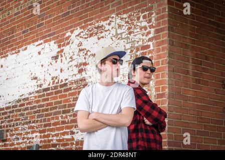 Dos hombres jóvenes con gafas de sol y gorros de pie espalda con espalda con los brazos cruzados contra la pared de ladrillo de estilo rústico en la ciudad Foto de stock