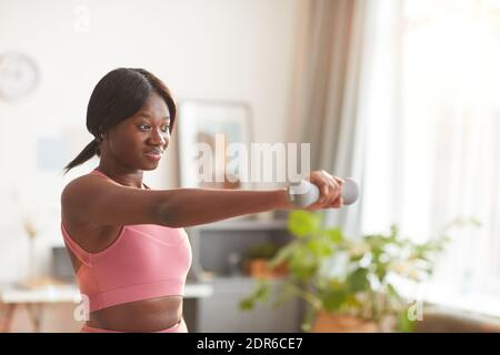 Retrato de cintura para arriba de mujer afroamericana que trabaja con pesas mientras hace ejercicio en casa, espacio de copia