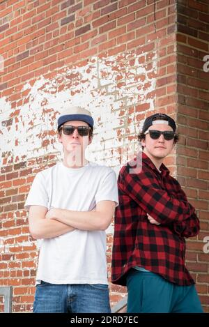 Dos hombres jóvenes con gafas de sol y gorros de pie espalda con espalda con los brazos cruzados contra la pared de ladrillo Foto de stock