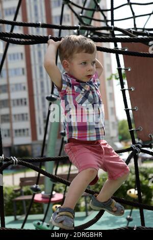 Niño jugando en red de escalada en verano