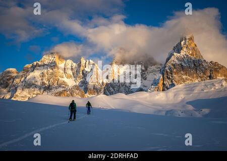 Dos hombres esquían en una alta llanura con una hermosa vista de los Dolomitas en el fondo. Lukas Oberschneider y Matthias Aigner, Passo Rolle, San Martino di Castrozza, Italia. Foto de stock