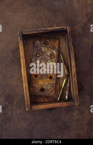 Pequeña caja de madera antigua que contiene dos bisagras de metal oxidado de la puerta y usó tornillos de latón y metal