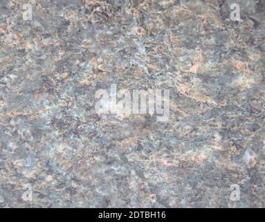 Granito azul pálido, superficie de piedra natural pulida con salpicaduras blancas y marrones en primer plano. Fondo, textura.