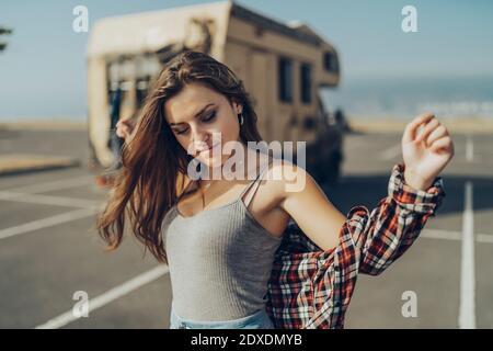 Mujer joven con los brazos estirados de pie en la carretera