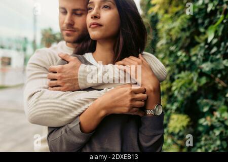 Joven hombre romántico abrazando a la mujer mirando fuera mientras que de pie parque