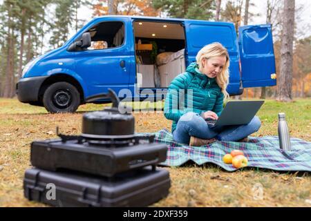 Mujer trabajando en el portátil mientras se sentaba en la manta de picnic en Cannock Chase
