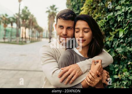 Joven pareja romántica abrazando mientras está de pie en el parque