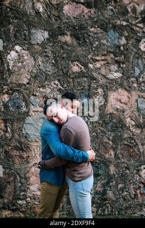 Hombres gays cariñosos abrazándose unos a otros mientras están de pie por piedra pared