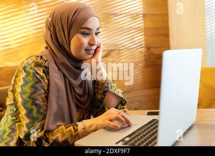 Mujer joven con hijab sentado con la mano en la barbilla mientras trabajando en el ordenador portátil en el café Foto de stock