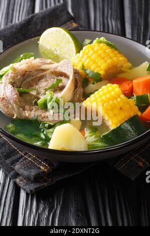 Caldo de res es una sopa tradicional mexicana de carne de vacuno hecha con trozos de carne y verduras primer plano en el plato de la mesa. Vertical