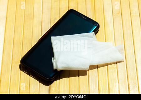 Smartphone moderno y una toallita húmeda, tejido húmedo sobre la mesa Teléfono móvil desinfección, limpieza, desinfección, tecnología e higiene durante covid 19