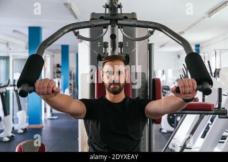 hombre entrenando en una máquina en el gimnasio. Céntrese en él.