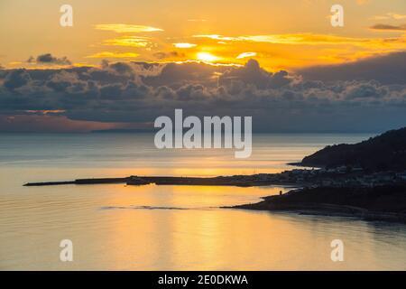 Charmouth, Dorset, Reino Unido. 31 de diciembre de 2020. El tiempo en el Reino Unido. Vista desde la cima del acantilado en Charmouth de la puesta de sol moody sobre la ciudad costera de Lyme Regis en la costa Jurásica de Dorset en el último día de 2020. Crédito de la imagen: Graham Hunt/Alamy Live News