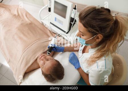 Vista superior de un cosmetólogo profesional con cara médica máscara mientras trabaja con cliente masculino