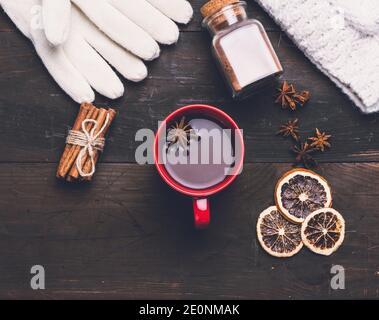 manoplas de punto y copa roja con una bebida en una mesa de madera marrón, vista superior.