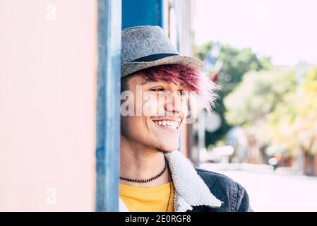 Feliz alegre joven alternativa adolescente sonrisa al aire libre en concepto de diversidad retrato -pelo violeta y sombrero para la gente moderna y elegante disfrutando ocio