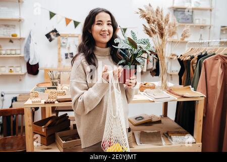 Mujer sonriente en la tienda ecológica posando para la foto con red bolsa y planta en maceta