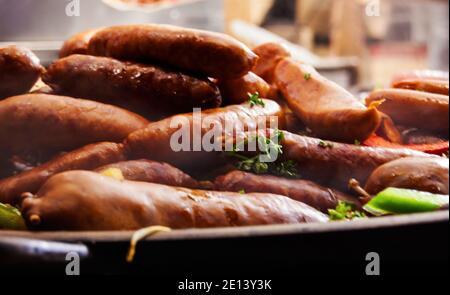 Salchichas tradicionales guisadas calientes con verduras en gran sartén en el mercado de la calle. Primer plano. Aumento del vapor. Mercado de Navidad en París.