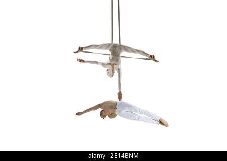 Para siempre joven. Pareja de acróbatas, atletas de circo aislados sobre fondo blanco de estudio. Entrenamiento perfecto equilibrado en vuelo, gimnasia rítmica artistas practicando con equipo. Gracia en el desempeño. Foto de stock