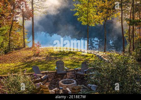 La niebla se levanta de un lago de montaña mientras el sol que se eleva ilumina el follaje otoñal que rodea una casa de cabaña de madera en el lago en las montañas del norte de Georgia.