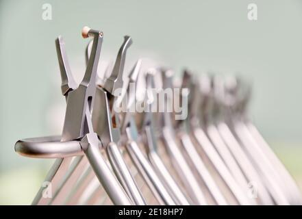 Vista de cerca del conjunto de varios instrumentos de acero inoxidable para aparatos ortopédicos en la clínica dental. Concepto de odontología, ortodoncia e instrumentos médicos.