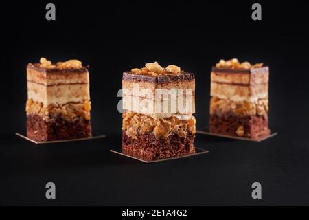 Vista frontal de trozos de postre fresco con galletas y mousse aislados sobre fondo negro. Vista de cerca de tres rebanadas cuadradas de pastel de chocolate marrón dulce con parte superior vidriada y frutos secos.