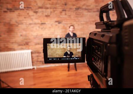 un primer plano de una cámara de vídeo, con grabación en curso mientras un hombre mira la cámara, en el entorno de estudio con una pared antigua, tomada en el antiguo puerto de Montreal.