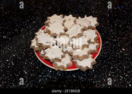 primer plano de deliciosas galletas de estrellas cubiertas de glaseado blanco caseras. Un bocadillo en un plato estaba sobre una superficie de cocina negra y brillante