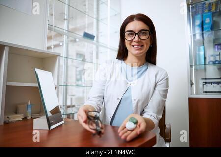 Oftalmólogo competente que demuestra un conjunto de contactos y gafas