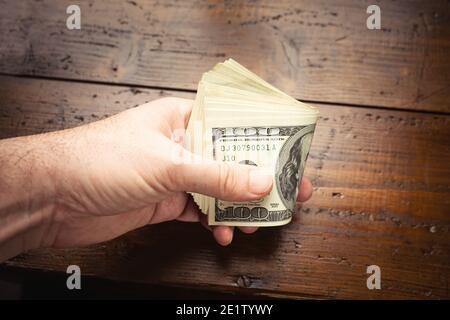 Mano con cien billetes estadounidenses sobre fondo de mesa de madera. Efectivo de billetes de cien dólares, moneda de papel moneda. Foto de stock