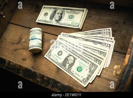 Cantidad de billetes de EE.UU. En pila de dinero y en rollo en cajón de madera. Dinero en efectivo de cientos de dólares, fondo de moneda de papel.