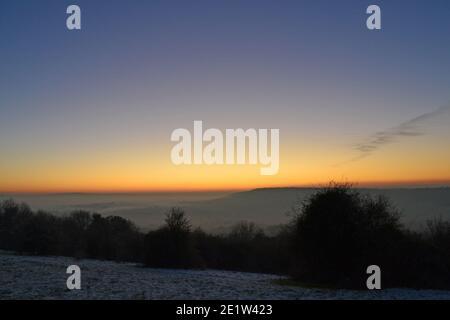 Espectacular puesta de sol en la brumosa luz de invierno en el North Downs, Fackenden Down, en Kent, cerca de Sevenoaks, crujiente, cielo claro sobre el enorme resplandor naranja, cielo azul