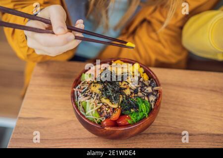 Mujer comiendo un cuenco de poke orgánico crudo con arroz y verduras de cerca en la mesa. Vista superior desde arriba horizontal