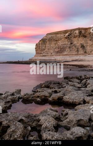 Una puesta de sol rosa sobre los acantilados de piedra caliza de Port Willunga playa en Australia del Sur el 1 de enero de 2021 Foto de stock