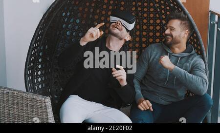 Mundo virtual. Alegre pareja gay usando gafas VR y relajándose en el balcón. Foto de alta calidad