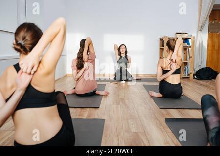 Mujeres flexibles practicando yoga en grupo, conectando los dedos detrás de sus espaldas