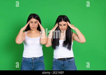 Las jóvenes gemelas se aferran a la cabeza con las manos. Concepto de fatiga y dolor de cabeza sobre un fondo verde.