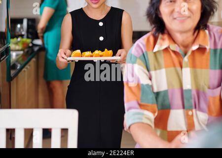 Imagen recortada de la mujer trayendo el plato de naranjas cortadas a mesa de cena para postre